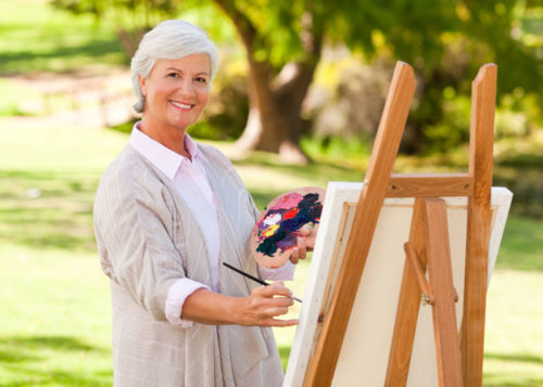 Woman an easel painting outdoors.